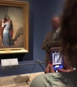 MusA - Museo Accessibile. Immagine che mostra un visitatore che inquadra con lo smartphone un dipinto in un museo.